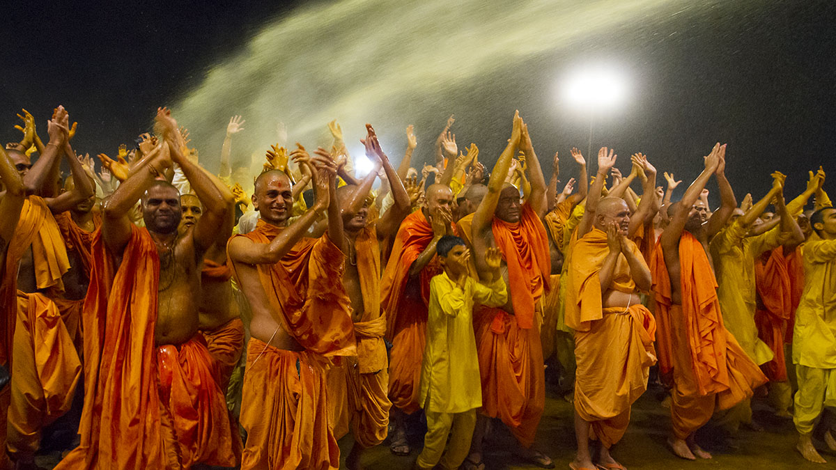 Swamishri showers sanctified colored water on sadhus and blesses them