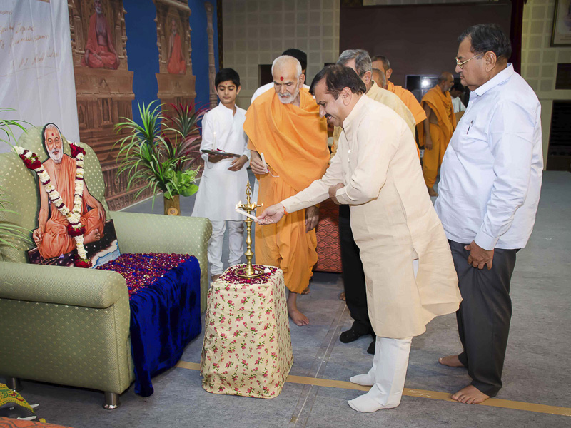 Pujya Mahant Swami and Shri Harinarayan Yadav light the inaugural lamp