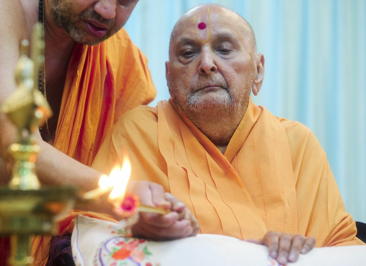 Swamishri lighting the inaugural lamp (deep-pragatya) at the start of the Sarangpur Mandir Shatabdi Mahotsav