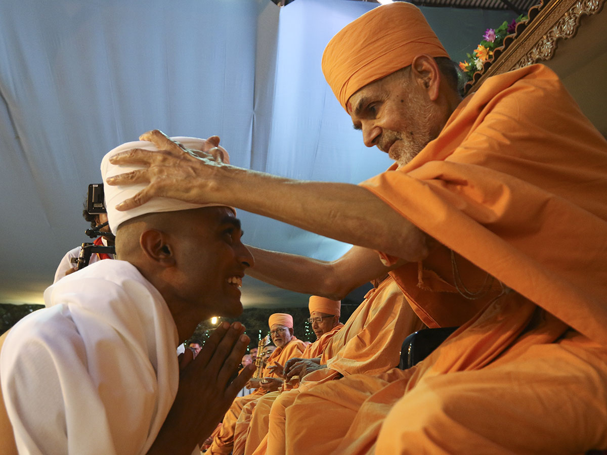 Pujya Mahant Swami puts on the 'paagh' for a newly initiated parshad