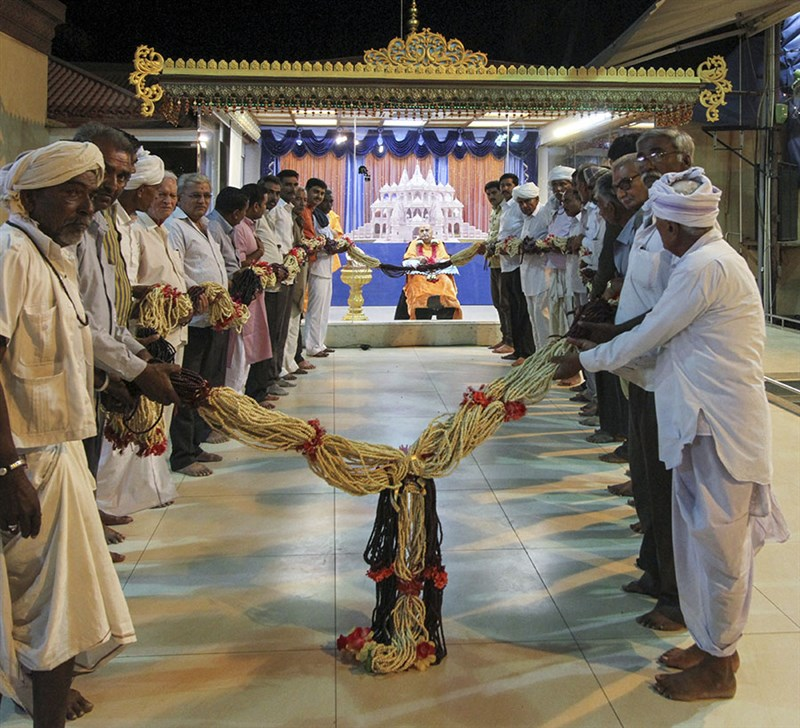 Leaders and seniors of Sarangpur village honor Swamishri with a garland