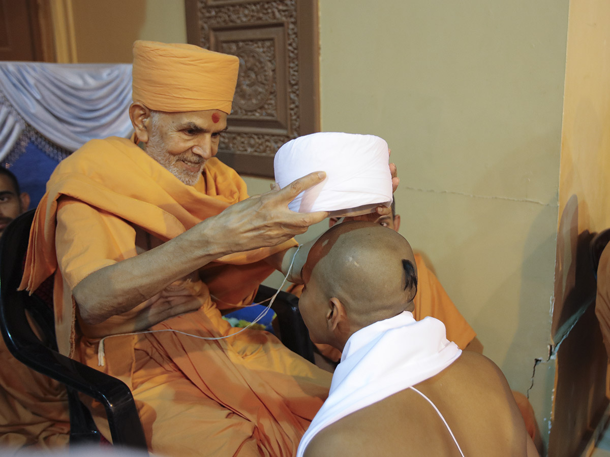 Pujya Keshavjivan Swami (Pujya Mahant Swami) puts on the 'paagh' for a newly initiated parshad