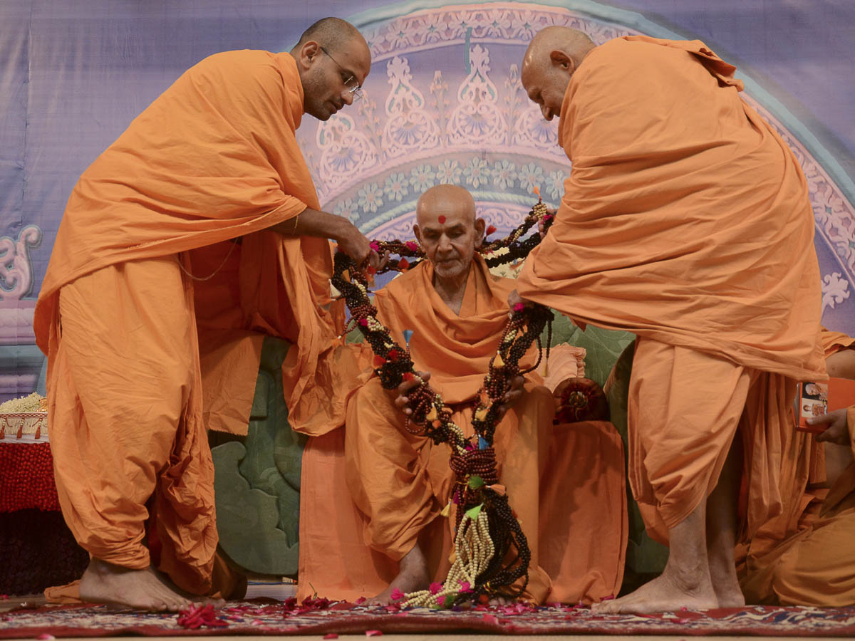 Sadhus honor Param Pujya Mahant Swami with a garland, 25 Aug 2016