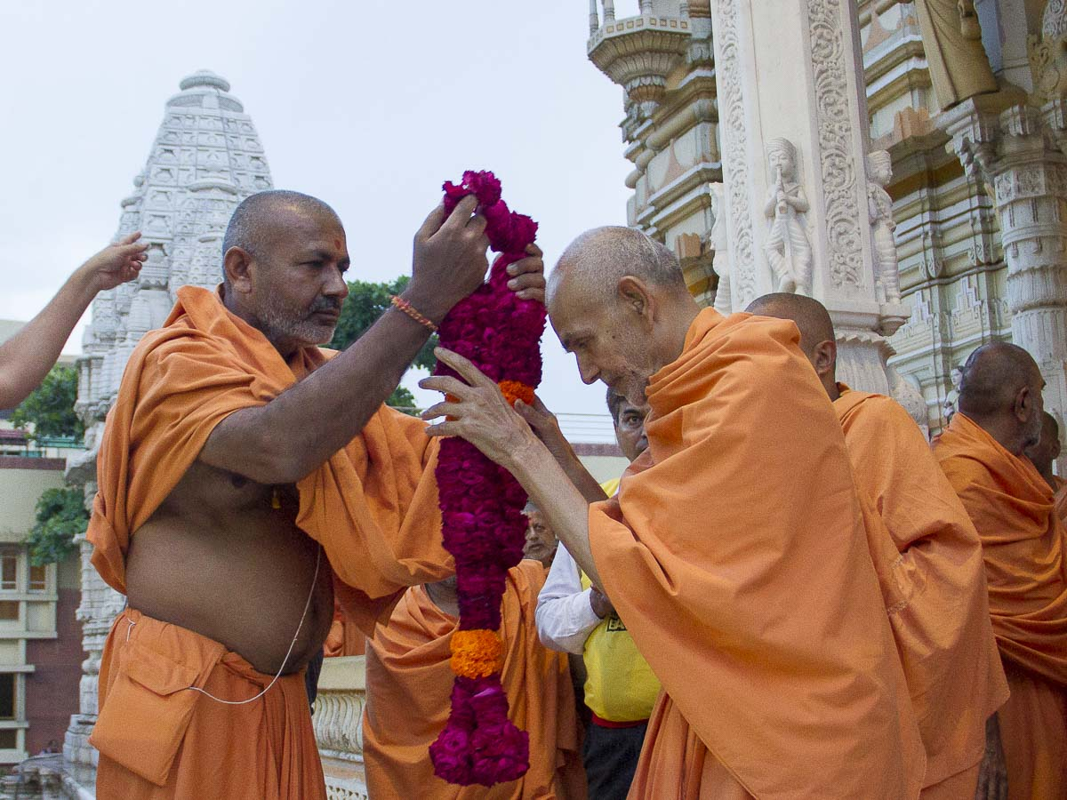 Atmakirti Swami welcomes Param Pujya Mahant Swami with a garland, 29 Aug 2016