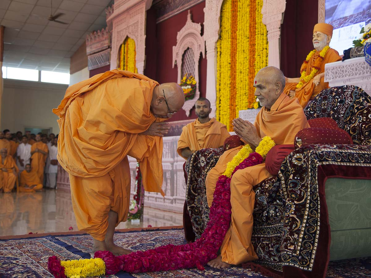 Pujya Tyagvallabh Swami honors Param Pujya Mahant Swami with a garland