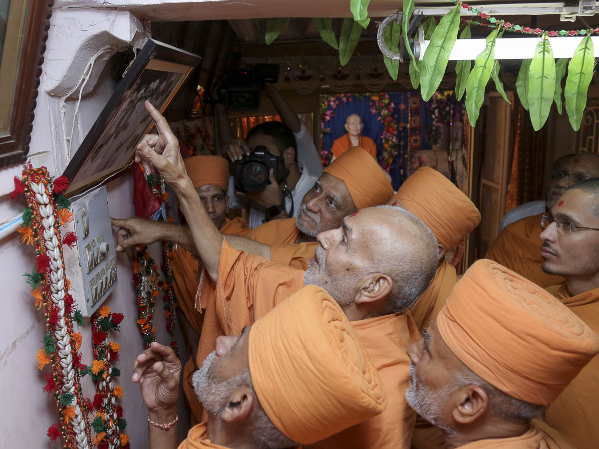 Param Pujya Mahant Swami observes a photo, 28 Sep 2016