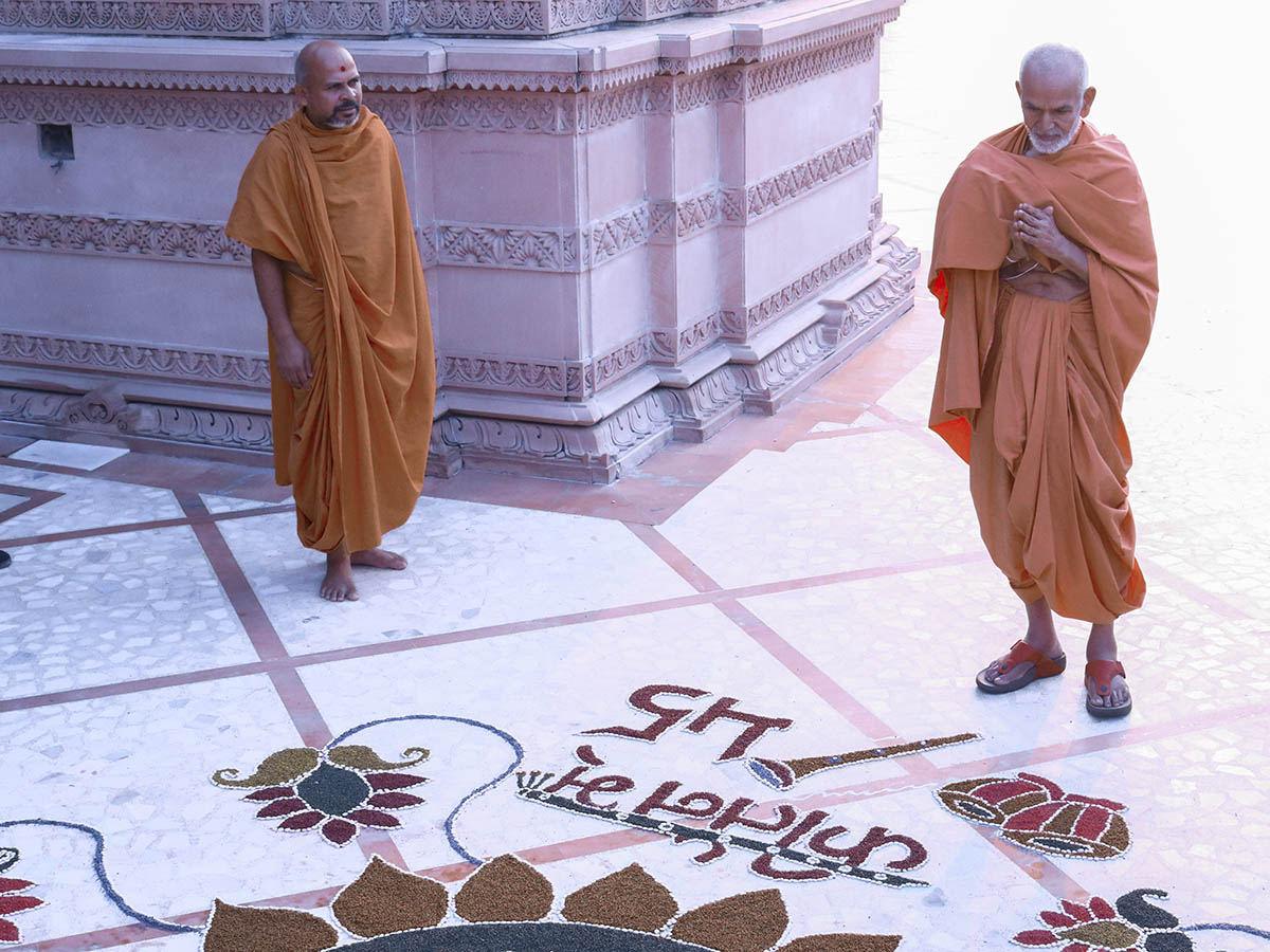 Param Pujya Mahant Swami observes a rangoli in the mandir grounds, 8 Oct 2016