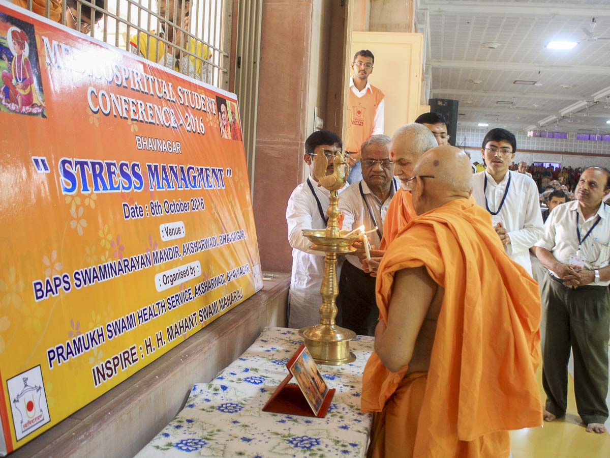 Param Pujya Mahant Swami and Pujya Tyagvallabh Swami light the inaugural lamp (deep-pragatya) for the Medico-Spiritual Student Conference 2016, 8 Oct 2016