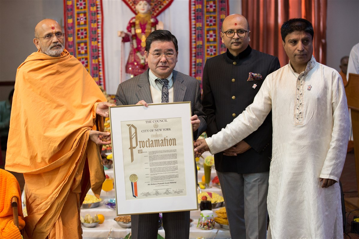 Councilman Peter Koo presents a proclamation to Pujya Yagnavallabhdas Swami and BAPS members
