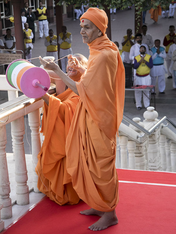 Param Pujya Mahant Swami Maharaj holds the string of a kite