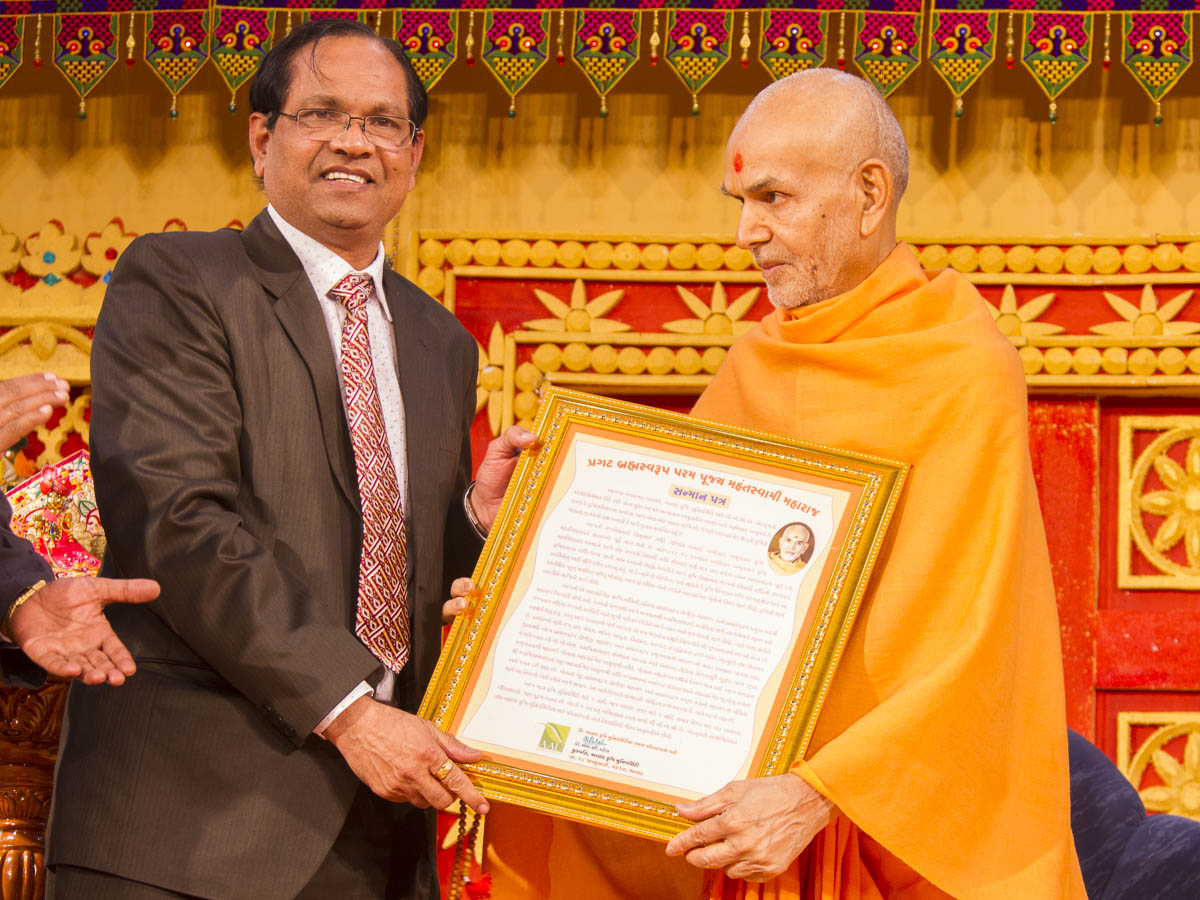 Dr. N. C. Patel, Vice Chancellor, Anand Agricultural University,  presents a certificate of honor to Param Pujya Mahant Swami Maharaj, 18 Jan 2017