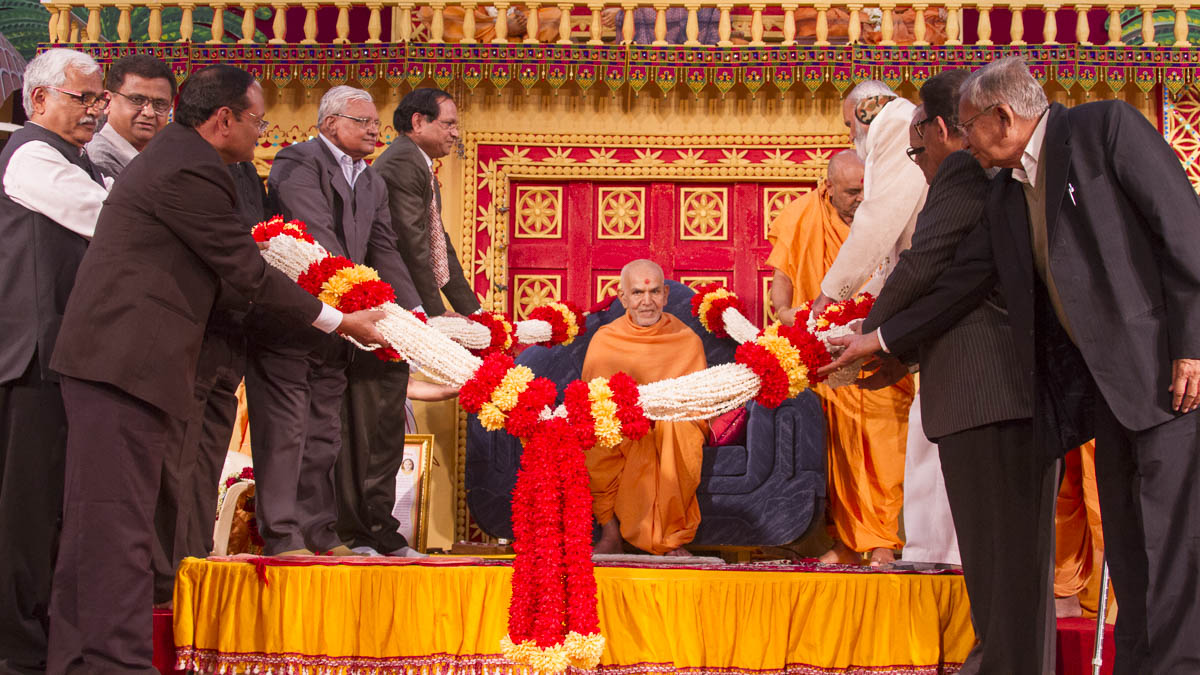 Shri C.L. Patel and other guests honor Param Pujya Mahant Swami Maharaj with a garland, 18 Jan 2017
