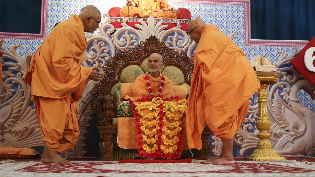 Pujya Kothari Swami and Pujya Tyagvallabh Swami honor Param Pujya Mahant Swami Maharaj with a garland and shawl on the 60th anniversary of Mahant Swami Maharaj's sadhu diksha, 29 Jan 2017