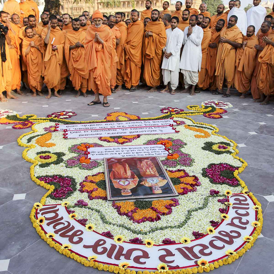 Param Pujya Mahant Swami Maharaj observes a flower rangoli in the mandir grounds, 4 Feb 2017