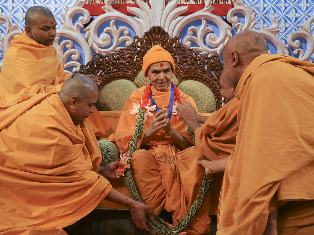 Sadhus honor Param Pujya Mahant Swami Maharaj with a garland, 10 Feb 2017