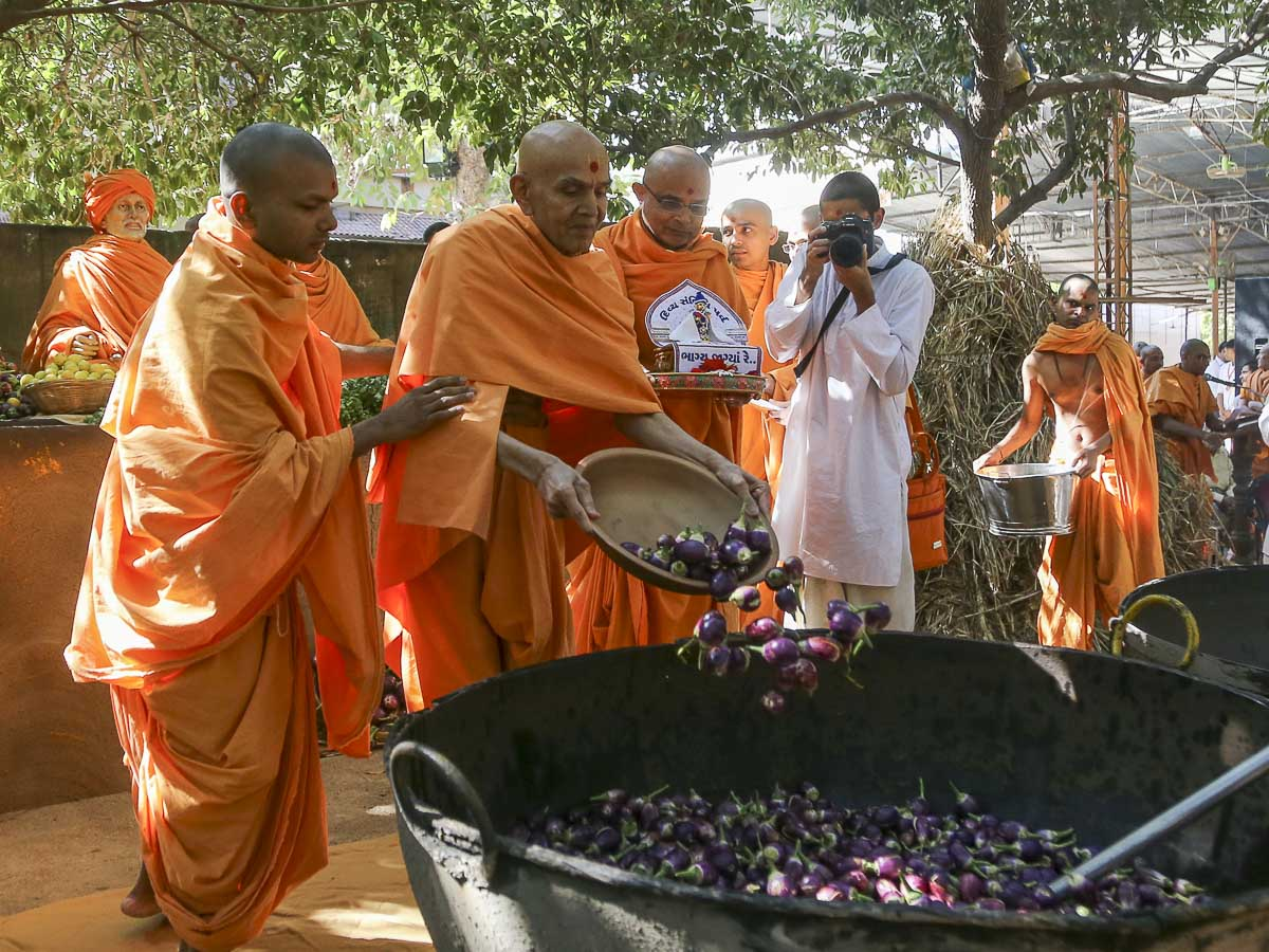 Param Pujya Mahant Swami Maharaj adds eggplants (ringna) to the shak mixture, 10 Feb 2017