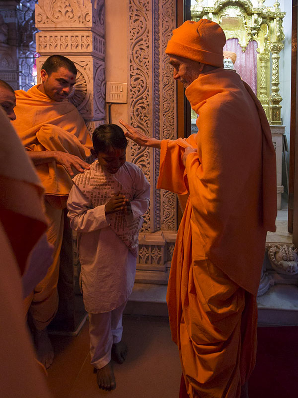 Param Pujya Mahant Swami Maharaj blesses a child, 25 Feb 2017