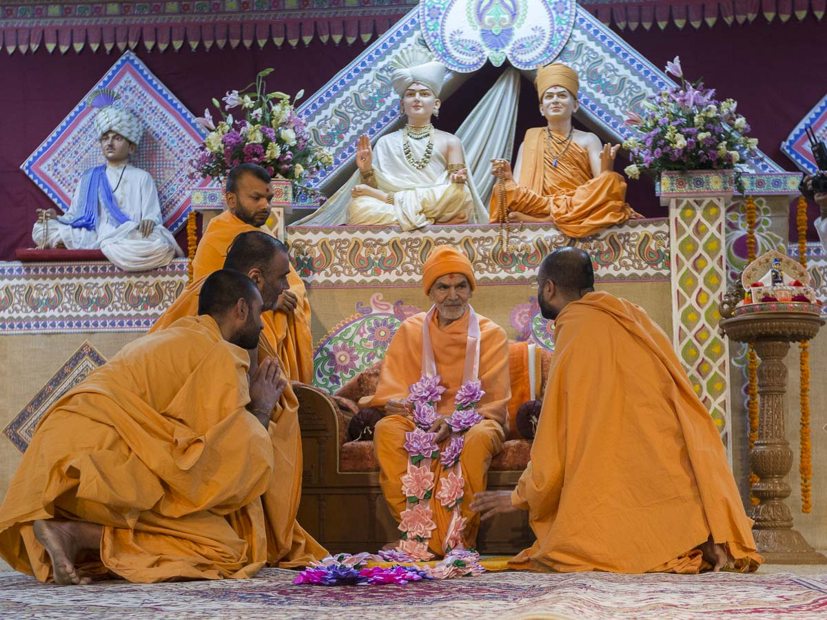 Sadhus honor Param Pujya Mahant Swami Maharaj with a garland, 25 Feb 2017