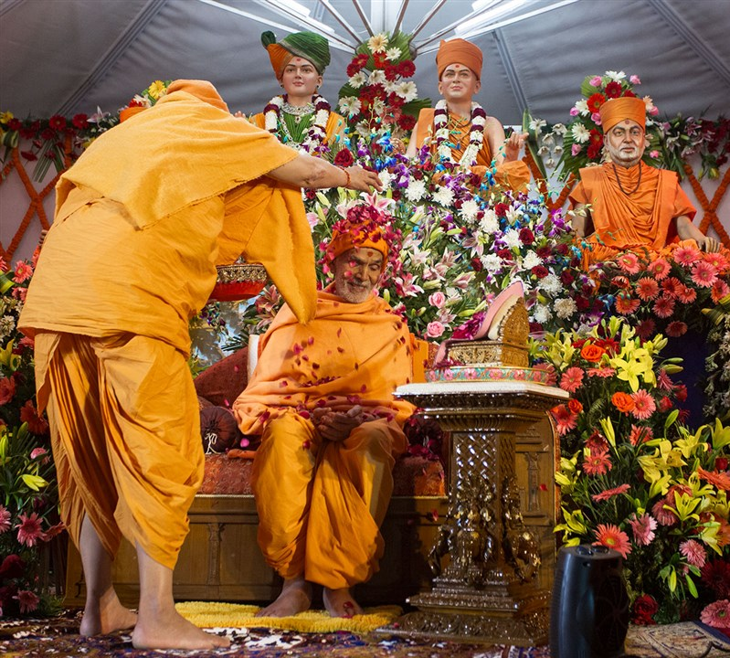 Pujya Ishwarcharan Swami showers flower petals on Param Pujya Mahant Swami Maharaj, 3 March 2017