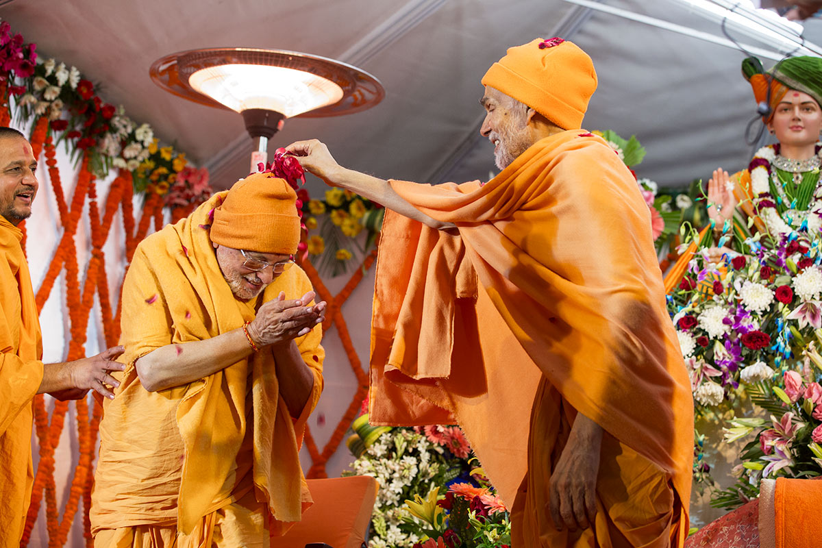 Param Pujya Mahant Swami Maharaj showers flower petals on Pujya Ishwarcharan Swami, 3 March 2017