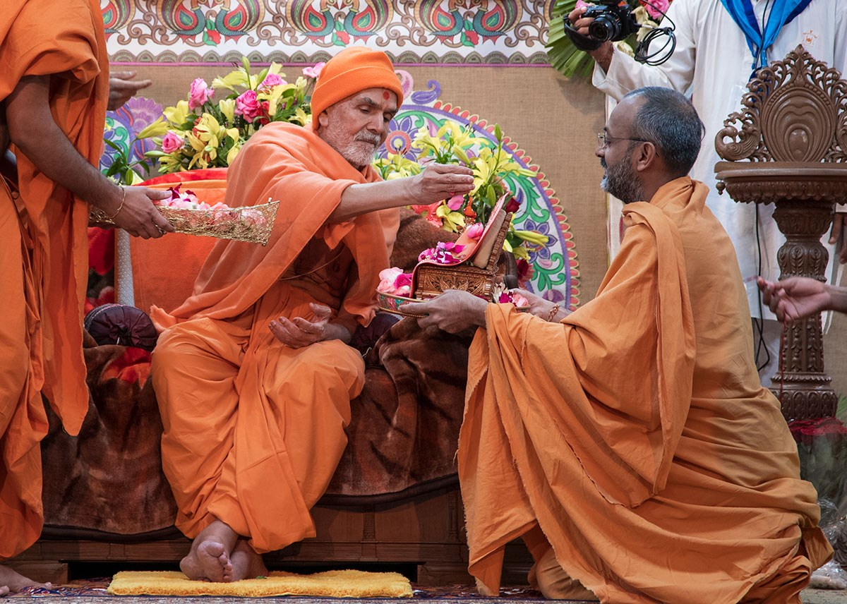 Param Pujya Mahant Swami Maharaj showers flower petals on Shri Harikrishna Maharaj, 4 March 2017