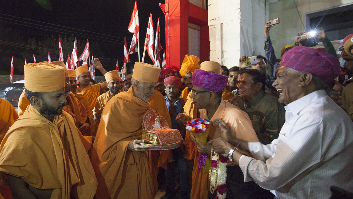 Kanubhai and Harshadbhai welcome Param Pujya Mahant Swami Maharaj with flowers and a garland, 4 Mar 2017