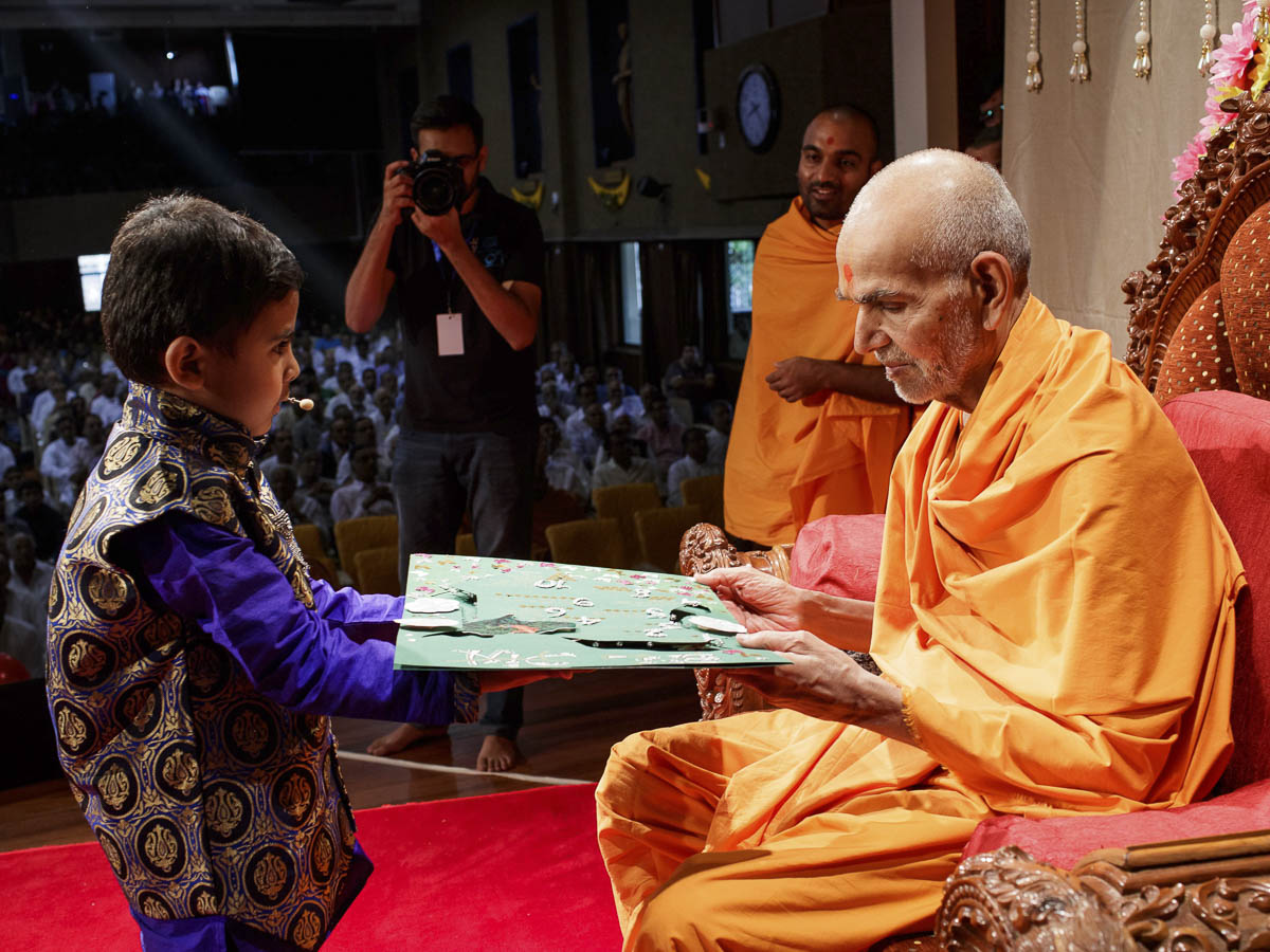 A child invites Param Pujya Mahant Swami Maharaj for the Bal Din assembly, 20 Mar 2017