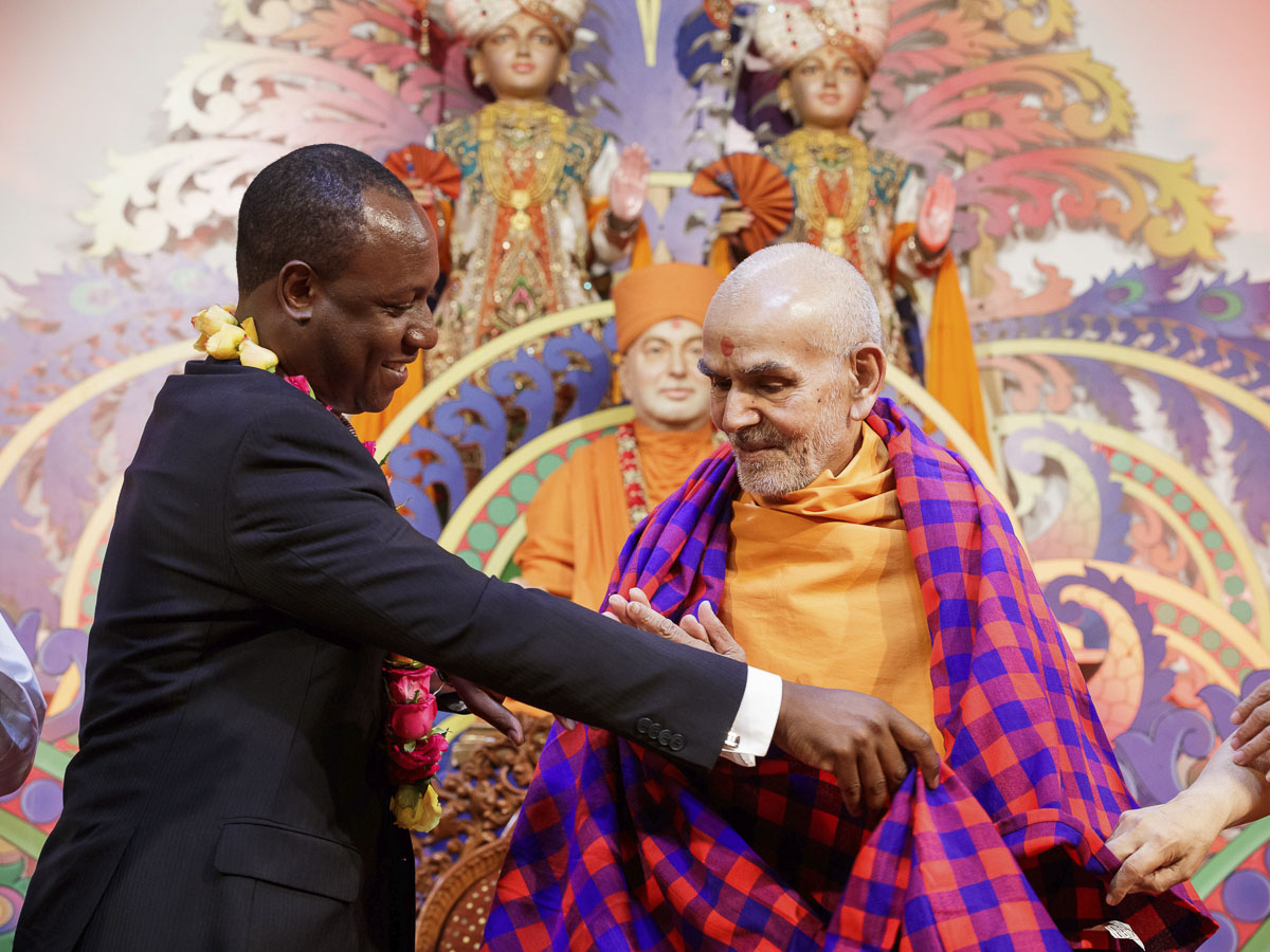 Hon. Jonathan Mueke, Deputy Governor of Nairobi County, honors Param Pujya Mahant Swami Maharaj with a shawl, 21 Mar 2017
