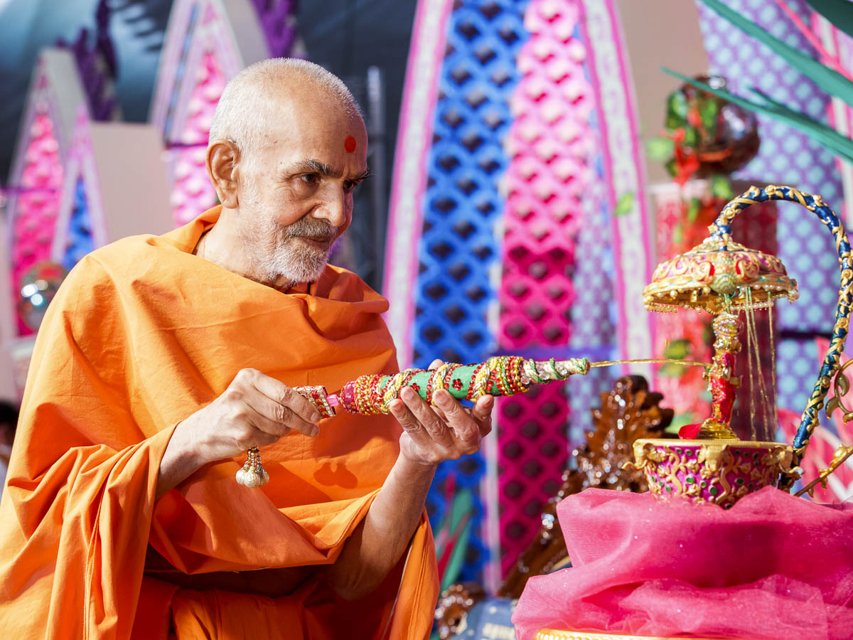 Swamishri sprays saffron-scented water on Shri Harikrishna Maharaj, 28 Mar 2017