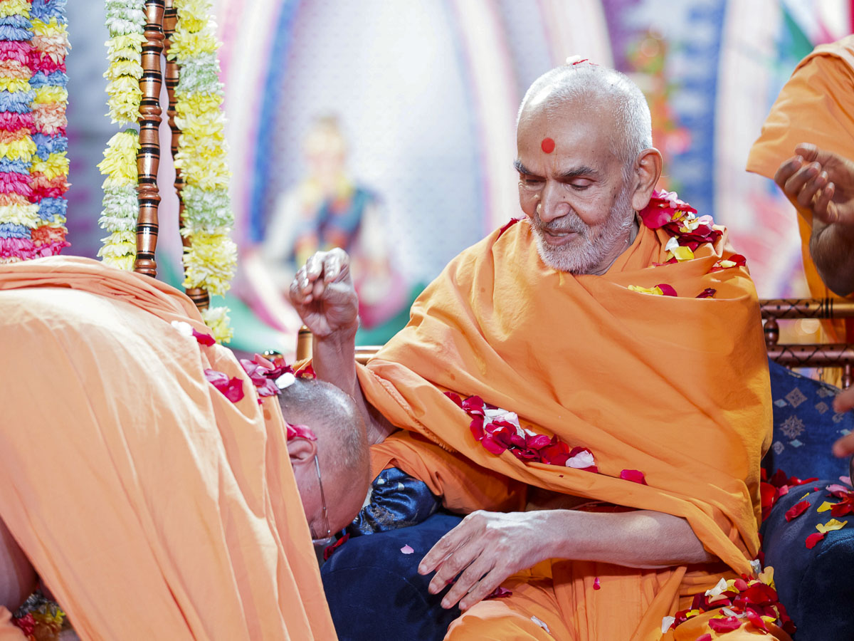 Swamishri showers flower petals on Pujya Ishwarcharan Swami, 28 Mar 2017