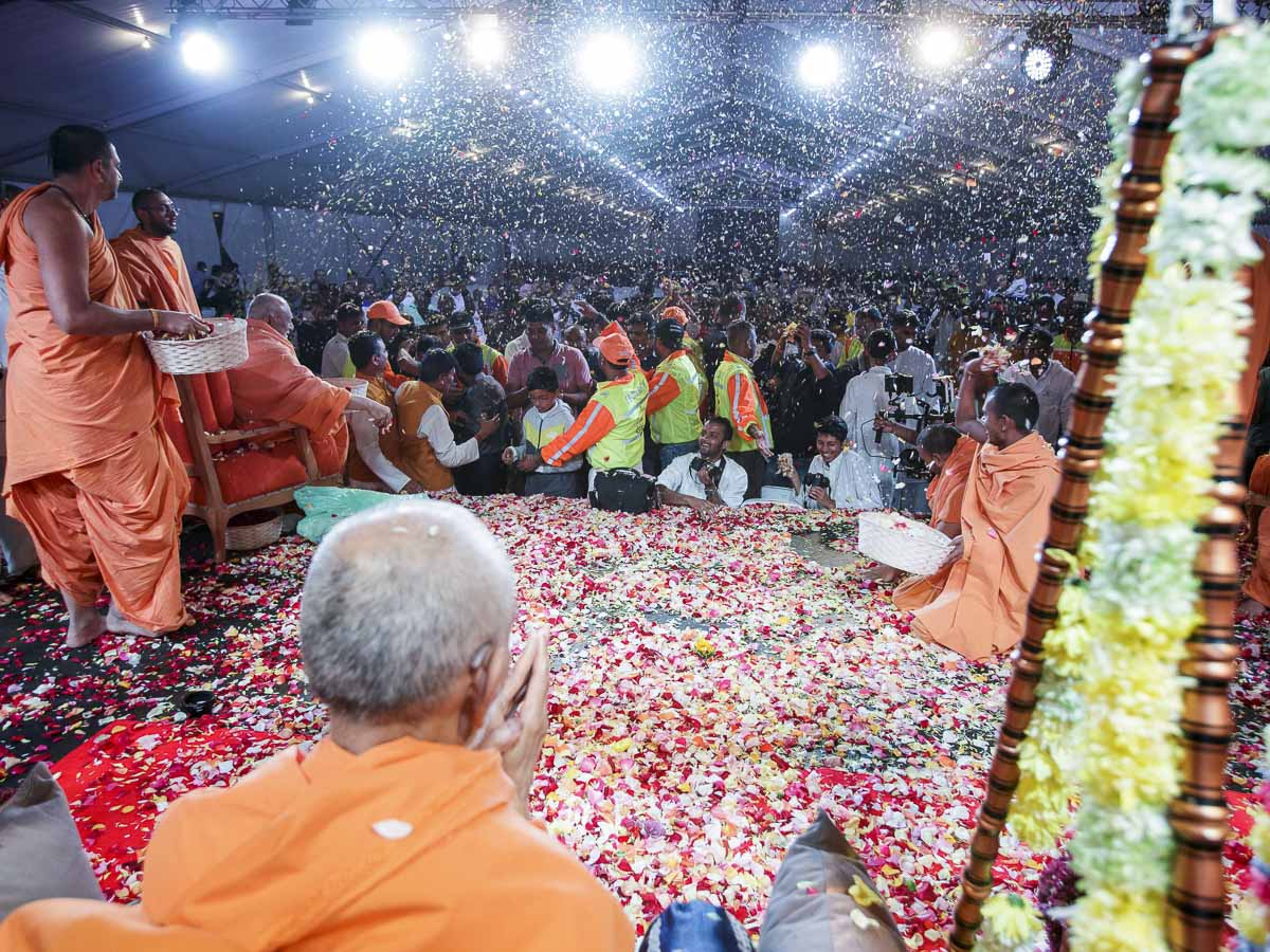 Devotees shower flower petals on Swamishri, 28 Mar 2017