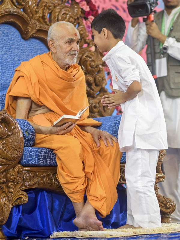 Param Pujya Mahant Swami Maharaj interacts with a child, 1 Apr 2017