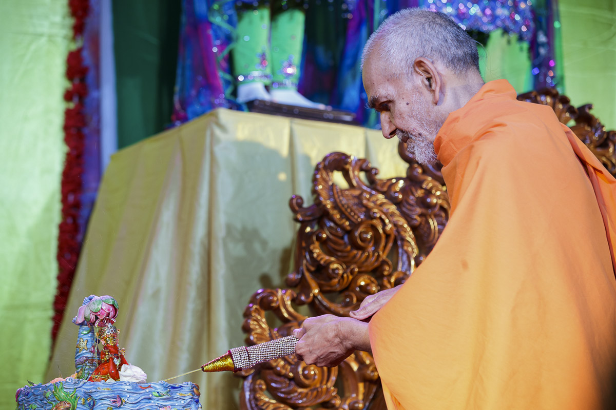 Swamishri sprays saffron-scented water on Shri Harikrishna Maharaj, 1 Apr 2017
