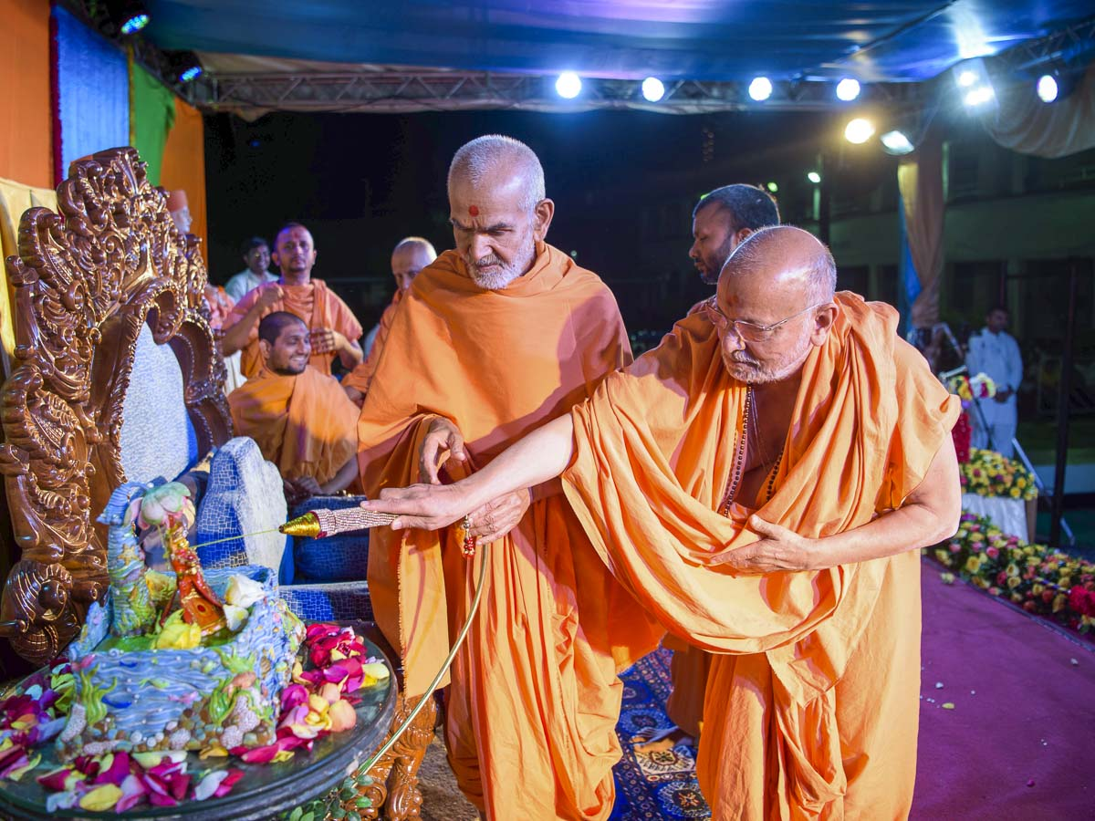 Swamishri and Pujya Ishwarcharan Swami spray saffron-scented water on Shri Harikrishna Maharaj, 1 Apr 2017