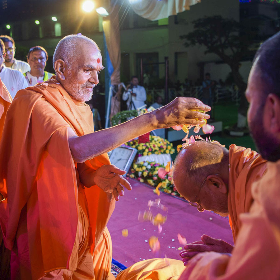 Swamishri showers flower petals on Pujya Ishwarcharan Swami, 1 Apr 2017