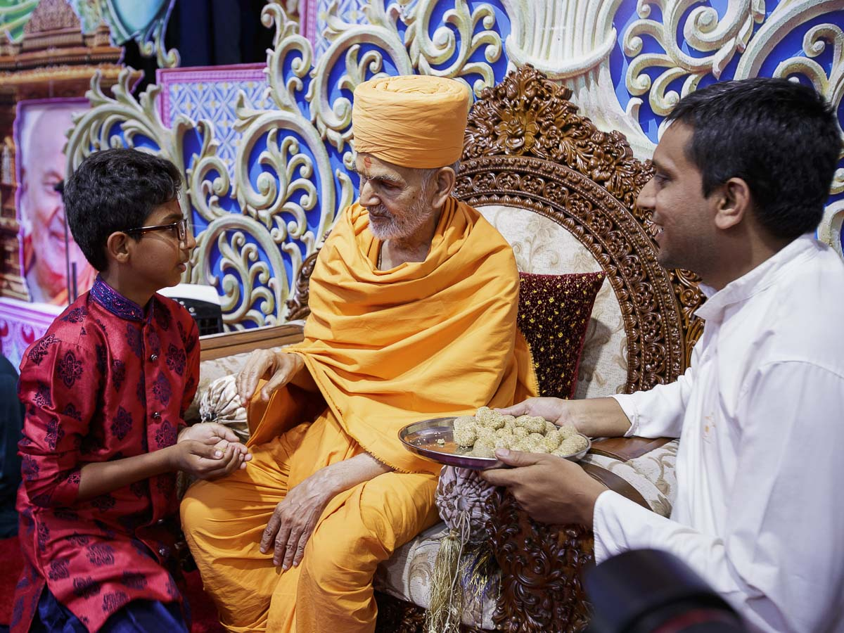 Swamishri gives prasad to a child, 7 Apr 2017