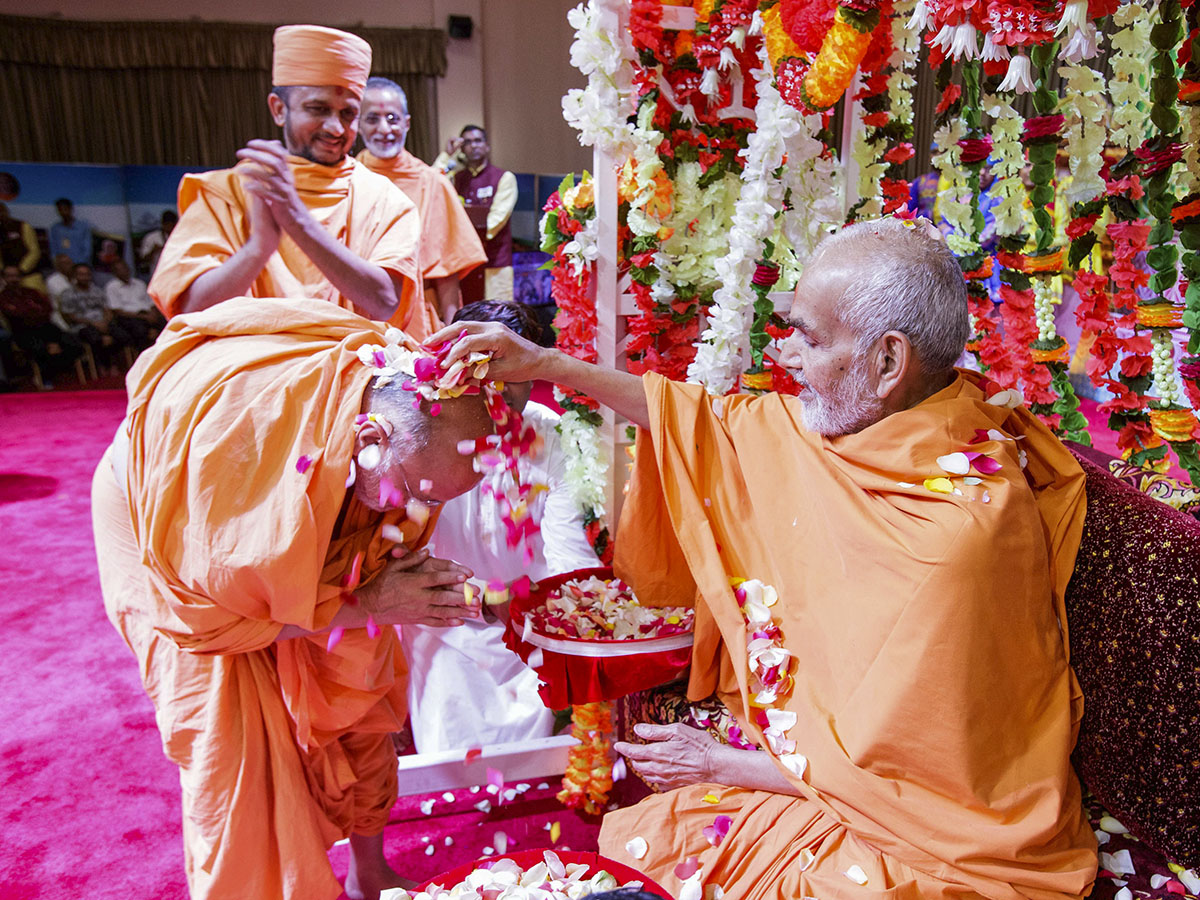 Swamishri showers flower petals on Pujya Ishwarcharan Swami, 8 Apr 2017