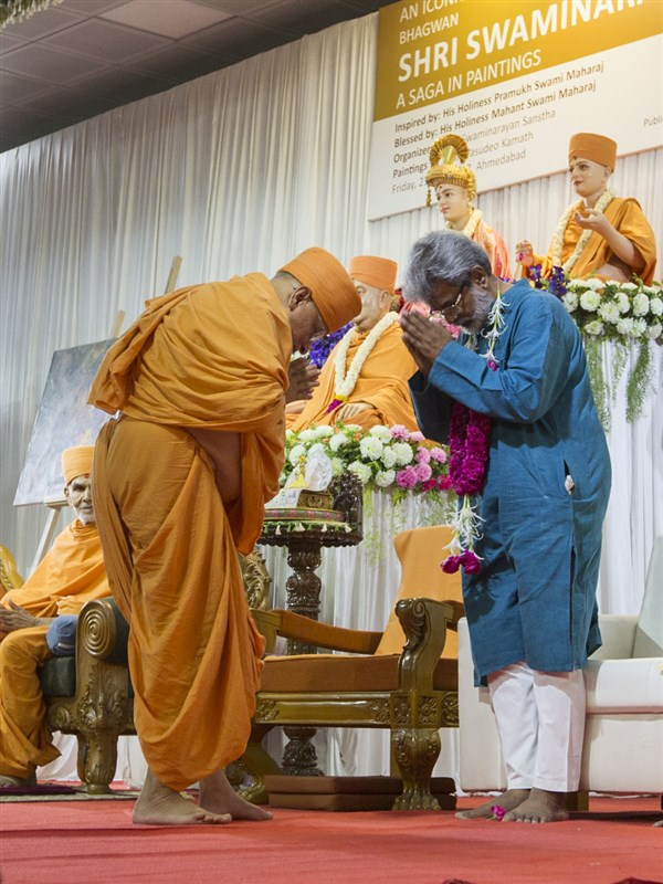 Pujya Ishwarcharan Swami honors Shri Vasudeo Kamath, the artist who painted all the paintings in the book, with a garland