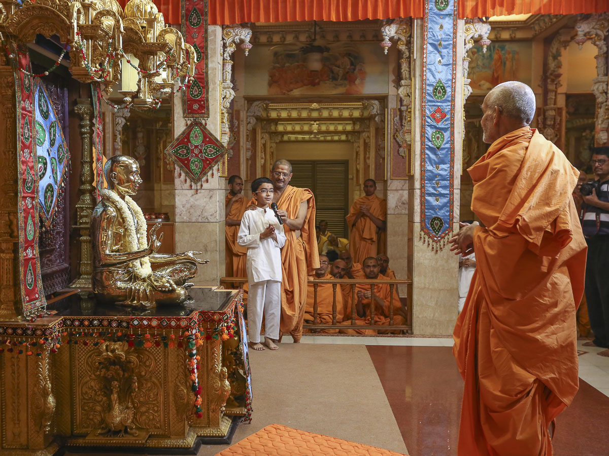 A child presents before Swamishri, 21 Apr 2017