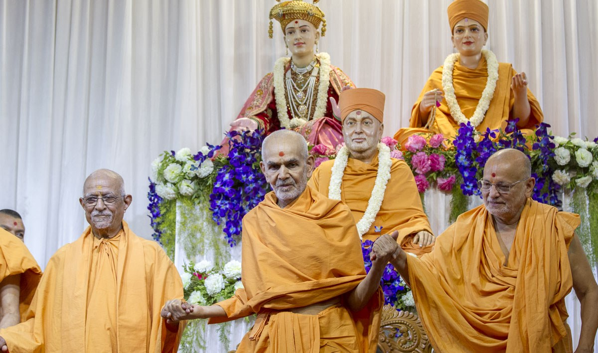 Pujya Doctor Swami and Pujya Ishwarcharan Swami join hands with Swamishri to symbolize unity, 22 Apr 2017