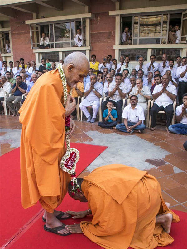 Atmakirti Swami honors Swamishri with a garland, 23 Apr 2017