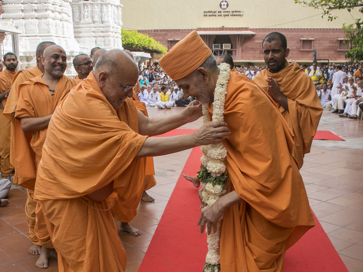 Pujya Ishwarcharan Swami honors Swamishri with a garland, 23 Apr 2017
