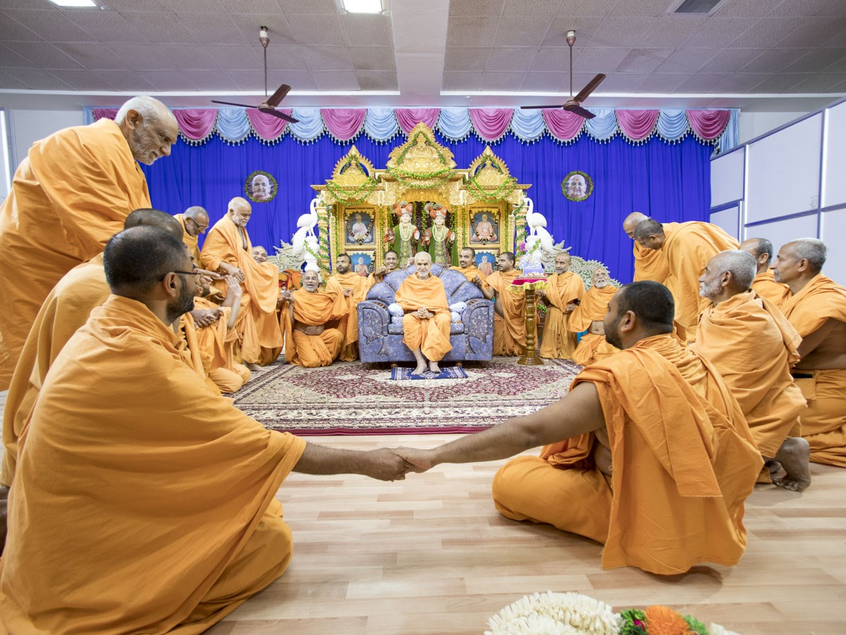 Sadhus join hands with each other and Swamishri to symbolize unity, 28 Apr 2017