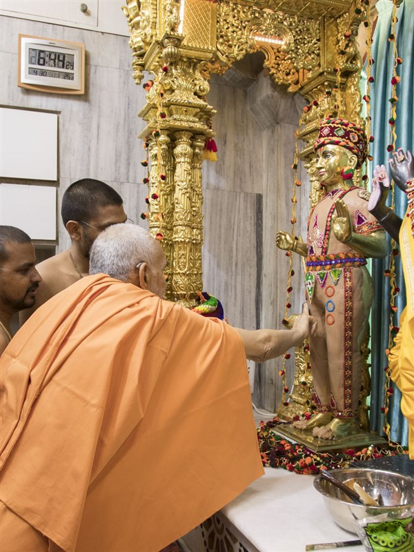 Swamishri applies chandan to the murti of Shri Harikrishna Maharaj, 30 Apr 2017