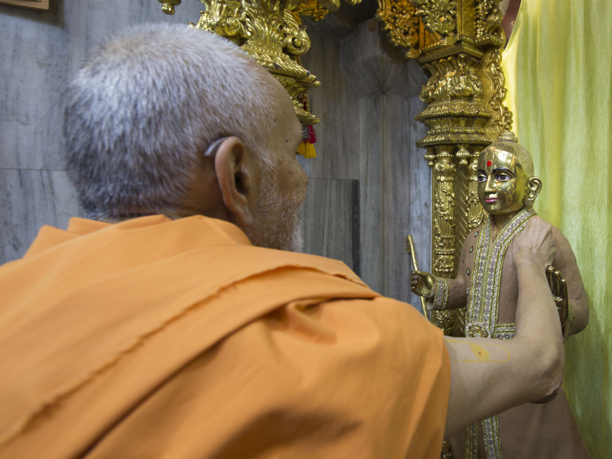 Swamishri applies chandan to the murti of Shri Harikrishna Maharaj, 1 May 2017