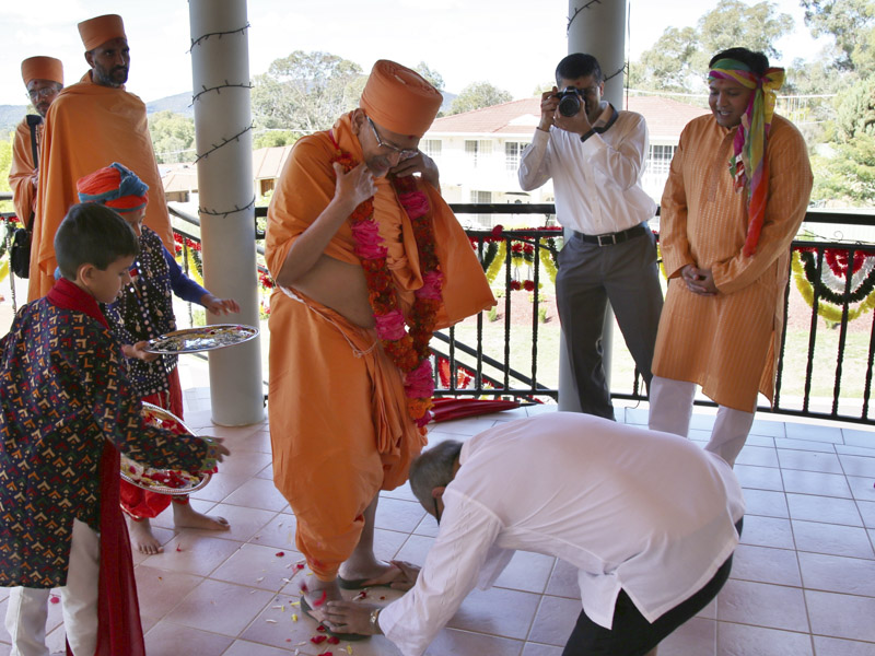 A devotee honors Pujya Tyagvallabh Swami with a garland