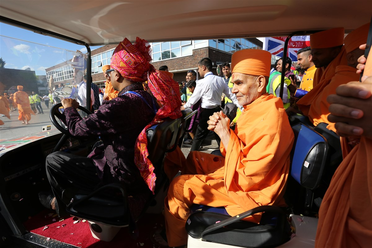 Swamishri greets devotees lining the welcome procession