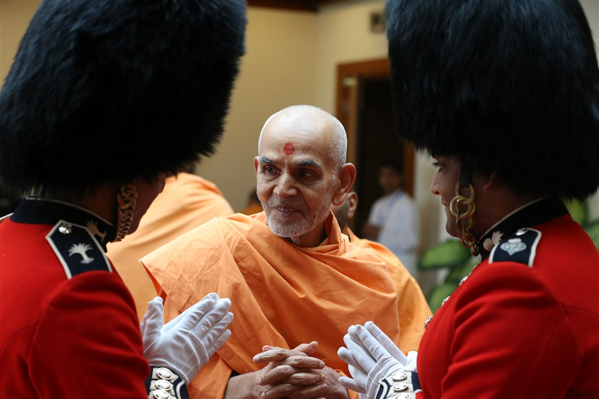Swamishri greeted by youths dressed as royal guards, leading him to the welcome assembly