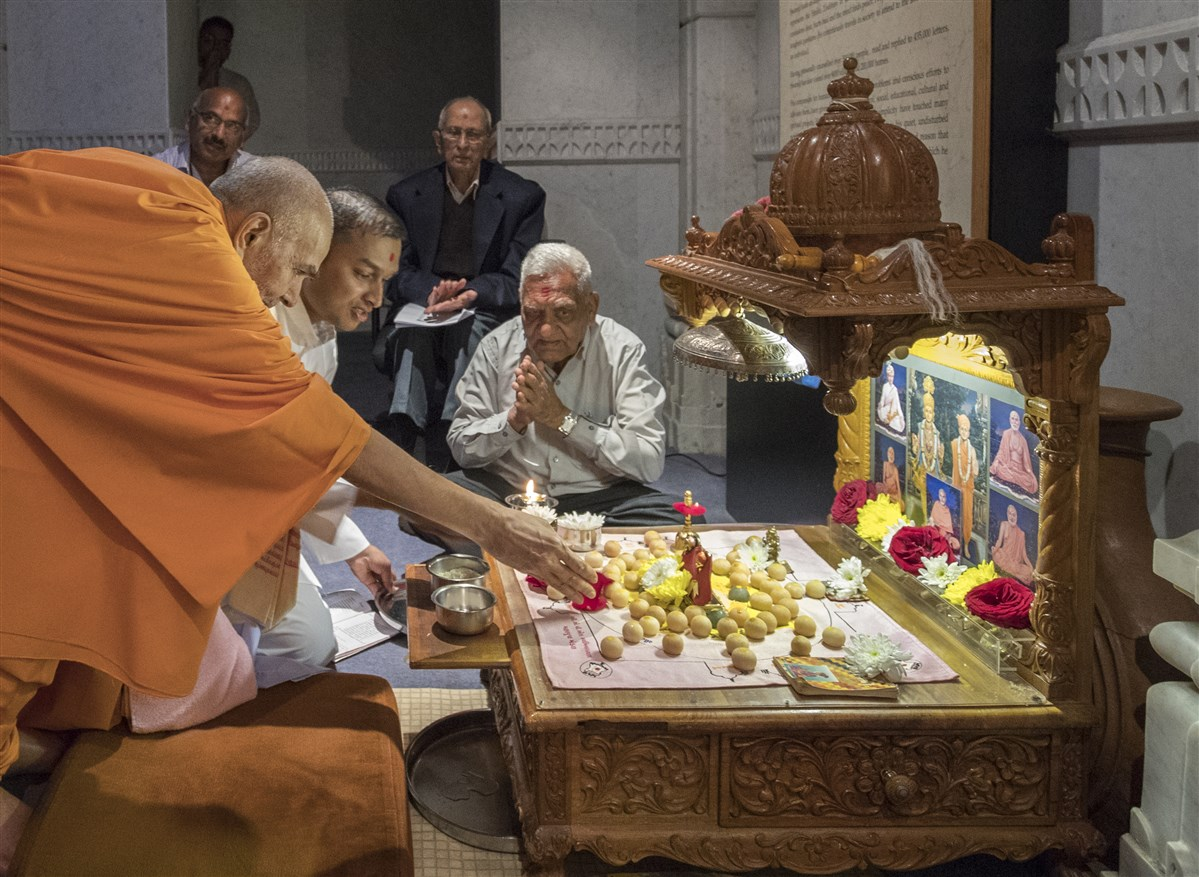 Swamishri offers a flower in the mahapuja