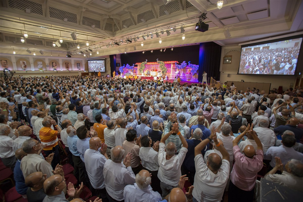 Devotees give a standing ovation to the performing sadhus